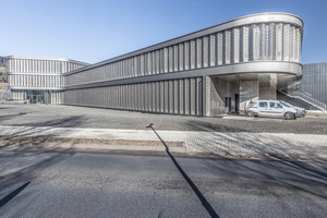 Die neue Firmenzentrale stellt sich nach außen durch eine umlaufende Fassade mit beweglichen Metallpaneelen dar