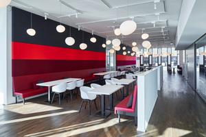 Farbige, gepolsterte und mit Stoff bespannte Wandflächen finden sich auch in der Firmenkantine als Absorberflächen wieder
