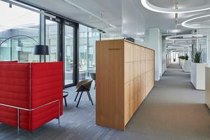 Textile Bodenbeläge, mikroperforierte Holzflächen an Büroschränken und gepolsterte Möbel in den offenen Räumen dienen der Raumakustik