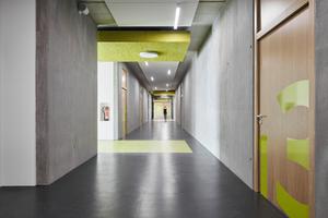 Im Kontrast zu den weißen Putzflächen und den unverkleideten Betonwänden markieren die grünen Akustikplatten Knotenpunkte
