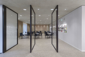 Im Erdgeschoss der Stadtbibliothek befindet sich ein Café, das allein durch große, drehbare Verglasungen abgetrennt ist. Beim Öffnen entsteht ein fließender Raum