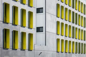 Die gelbgrün eloxierten Fensterlaibungen rhythmisieren das Gebäude