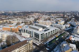 """Das Luftbild zeigt, wie der gesamte Gebäudekomplex die """"Neue Mitte"""" im Stadtteil Herrenhausen bildet. Im Vordergrund ist die Stadtbahnhaltestelle zu sehen"""