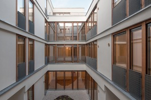 """<irspacing style=""""letter-spacing: -0.01em;"""">Die Fensterbänder der Fassade werden durch eine vertikale Lärchenholzverschalung gegliedert. Vor den Fenstern und an den Balkonen sitzen schlichte Metallgitter als Absturzsicherung</irspacing>"""