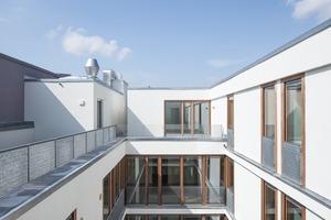 Die Erschließung im Staffelgeschoss über die Dachfläche hat mit den Wohnungen und ihren Freiflächenentlang des Erschließungsweges und den weißen, kubischen Aufbauten, Lichtschächten und Abstellboxen einen fast maritimen Charakter