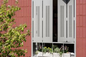 Faltläden aus Aluminium ermöglichen eine maximale Verschattung der gesamten Fensterhöhe. Die schlanke Laufschiene im unteren Abschluss der Fenster dient nicht nur der stabilen Führung der Faltläden, sondern ermöglich die Belichtung der Blumenkästen auf den Fensterbänken