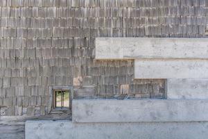 Außen stoßen die neuen und alten Materialien ebenso aufeinander wie Innen. Die 43x43cm großen und unterschiedlich langen Balken des Leichtbetons und die erhaltenen Holzschindeln bilden einen faszinierenden Kontrast