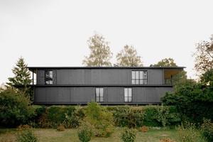 Ein Einfamilienhaus wurde durch dieses dreigeschossige Mehrfamilienhaus aus schwarz geölter Fichte ersetzt