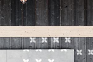 Unregelmäßig angeordnete blütenförmige Perforationen in den Schindeln betonen die besondere Nutzung und sorgen für ein stimmungsvolles Spiel mit Licht und Schatten