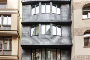Stufenweise schiebt sich die Fassade über dem Erdgeschoss nach vorn. Statt in üblicher Rechtsdeckung wurde die Giebelfront des Dachgeschosses mit einer Links- bzw. Rechtsdeckung versehen und so spiegelbildlich gestaltet