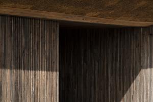 Neben Reet kam auch vorpatiniertes Robinienholz als Fassadenmaterial zum Einsatz, u.a. um die Bestandsbauten in das neue Gebäudeensemble formal zu integrieren