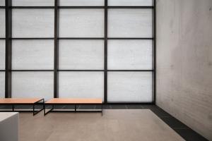 Geschlossen wird das obere Foyer durch eine mit dünn geschnittenen Steinplatten gefüllte Pfosten-Riegel-Konstruktion. Dahinter die Fassade des Pergamonmuseums