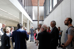Im Hintergrund einer der historischen Gründungspfähle als Ausstellungsstück inszeniert. Davor die Architekten u. a.