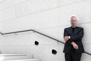 David Chipperfield auf der großen Treppe in seiner Architekturlandschaft Museumsinsel