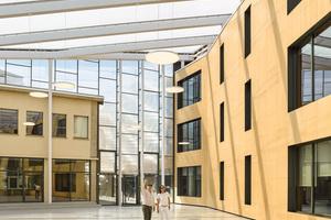 Statt einer Überkopfverglasung wählten die Architekten Luftpolster als Dachhaut. Diese macht das Licht diffuser und ist leicht, zudem wirkt der Raum ohne das grünliche Licht, das durch herkömmliche Verglasungen in die Räume gelangt, eher als Außenraum