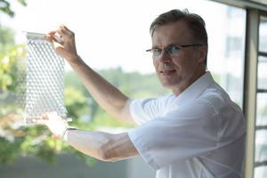 Prof. Stefan Schäfer demonstriert am Prototypen, wie der textile Sonnenschutz funktioniert. Durch Auseinanderziehen des Stoffs entstehen Öffnungen, die Licht durchlassen