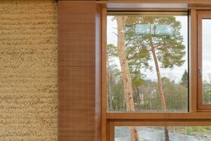 Die Innenansicht der Lehmfassade ist homogener und weniger rau. Die Fens-ter sind mit Akustikpaneelen aus Holz eingefasst