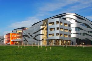 Für die dynamische Gestaltung der Fassade kamen rund 20000m² Aluminiumpaneele zum Einsatz eloxiert im Naturton sowie Dunkelblau, verschiedenen Rot-, Orange- und Gold-Nuancen und einer Holzstruktur. Jedes Paneel ist individuell, innerhalb des Musters gibt es keine Wiederholungen