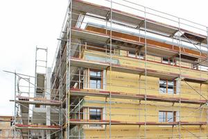 Brettsperrholzkonstruktion mit Holzfaser-WDVS bis zum 3. OG. Das zurückspringende Attikageschoss ist mit einer holzfasergedämmten, vorgehängten hinterlüfteten Fassade bekleidet