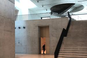 Außen unscheinbarer Bestand (rechts), innen ist vieles ganz anders … Blick ins Foyer mit Lichtfuge zum Bestand sowie Frei- und großer Wendeltreppe oben