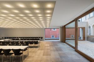 Im Erdgeschoss unter der Synagoge<br />öffnet sich der Gemeindesaal – der auch für kulturelle Veranstaltungen genutzt wird – mit großen Glasflächen zum<br />Innenhof und zur Stadt. Die Installationen für die Beleuchtung in der Decke<br />wurden in die tragende Kassettendecke aus Stahlbeton integriert