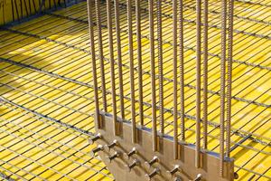 Am Fußende der Stützen gibt es eine Kopfplatte aus Stahl mit einem Zentrierdorn. Jede Stütze ist mit hochfestem Zement kraftschlüssig mit dem<br />Boden verbunden