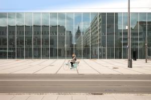 Wo bitte schön ist hier der Eingang? Glasquader spiegelt Alltagsarchitektur. Dahinter ein Park<br />