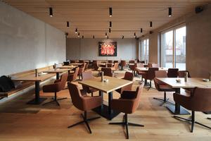 Holz, Beton, Leder sind die Materialien, die im Restaurant dominieren. Hier im Erdgeschoss, wie auch im Untergeschoss, wurde das Gebäude in massiver Bauweise errichtet, erst darüber beginnen die Module