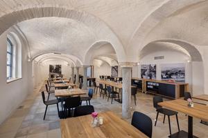"""<irspacing style=""""letter-spacing: 0em;"""">Der Frühstücksraum im Erdgeschoss. Die Gewölbe des Bestands waren starkt verformt, da das Gebäude kein Fundament besaß. Zur Unterfangung der Außenmauern und der Stützen wurden Fundamente gebaut. Danach erhielt der Raum einen neuen Fußbodenaufbau mit Fußbodenheizung, die alten Bodenplatten wurden gesäubert und wieder eingesetzt</irspacing>"""