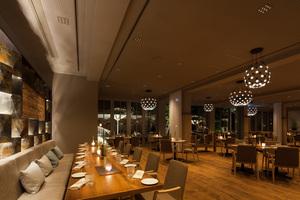 Tages- und Nachtwirkung des Restaurants Treibgut im Hotel Lago, Ulm: Während in der Nacht eine introvertierte Lichtstimmung die Konzentration auf die Tischflächen lenkt, wird am Tag der Außenraum mit einbezogen und die Tageslichtwirkung bis in den hinteren Raumbereich getragen
