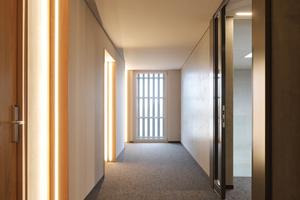 Treppenhaus und Flure sind zweckmäßig und dem Materialkonzept entsprechend mit viel Holz gestaltet. Die Lichtlinien helfen bei der Orientierung