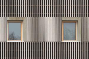 Die Fassadengestaltung der Hoffnungshäuser zeigt eine lineare Struktur aus Holzleisten