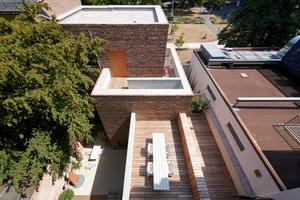 Die beiden Wohneinheiten über der im Hinterhof gelegenen Bürofläche erschließt man über das Eingangstreppenhaus und eine anschließende, frei bewitterte Terrassenfläche