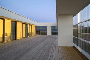 """<irspacing style=""""letter-spacing: 0em;"""">Alle oberirdischen Geschosse werden mit einer vorgesetzten Hülle </irspacing>aus gewellten Polycarbonatplatten (transparente Ausführung) und Alu-Unterkonstruktion ausgeführt. Große Teile der Fassade sind mit beweglichen Schiebeelementen ausgestattet. Die transparente Fassade wirkt energetisch wie ein Puffer, bildet den Witterungsschutz für die rohe Fassadendämmung und streut Tageslicht in die Innenräume"""