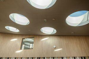 22 runde LAMILUX Flachdach-Fenster F100 bringen Tageslicht in die Räume des Kindergartens. Die runden Formen fügen sich in den geschwungenen Deckenverlauf ein und das bei dem sehr großzügigen Durchmesser von 1,50m