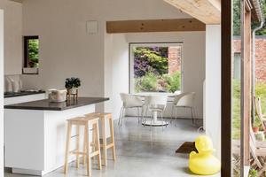 Die Wandflächen zwischen dem ehemaligen Flur und dem Wohnzimmer wurden auf das konstruktiv notwendige<br />Minimum reduziert. Dadurch schufen die Architekten einen von der Straße bis in den zweiten Anbau durchgehenden, offenen Raum, der sich durch großformatige Glasschiebetüren visuell auch ins Freie fortsetzt