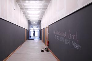 """Vor einem Übungsraum: Schuhe aus und die Tafel beschrieben. Ansonsten sind die Flure lang, die Wände mit Tafelfarbe unter der """"Wasserline"""" gestrichen: Hier dürfen die Lernenden alles aufmalen/schreiben, bis es Ende eines jeden Monats wieder abgewischt wird"""