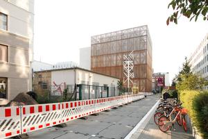 Winkt in den Straßenraum (Zinnowitzer Straße) herüber: der mit Holz verkleidete Bühnenturm der HfS Ernst Busch