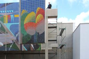 Montage der letzten Platte: Mosaikplättchen auf Betonscheibe, die mittels Stahlwinkel am Betongerüst gehalten wird