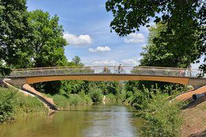 Die integrale Massivholzbrücke mit frei sichtbarem und nur konstruktiv geschütztem Holzüberbau betont ihren Anspruch auf nachhaltiges Bauen. Sie ist ein ebenso innovatives wie schönes Bauwerk. Mit ihrer sanft geschwungenen Gestalt fügt sich die knapp 40 m lange Brücke hervorragend in die Parklandschaft der Rems ein. Entwurf: Thorsten Helbig, Knippers Helbig GmbH