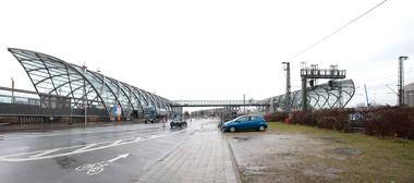 Zwischen den Bahnhöfen eine Straße und die Hauptschlagader Bahnverkehr (Güter/Personen) von Nord nach Süd und umgekehrt. Überbrückt von einer schmalen Glasröhre, die den Personenaustausch zwischen S-Bahn und U-Bahn möglich macht.