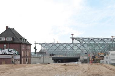 Hinter dem flacher gekrümmten Korb der S-Bahnstation vorne das Dach der bereits Ende 2018 eröffneten U-Bahnstation