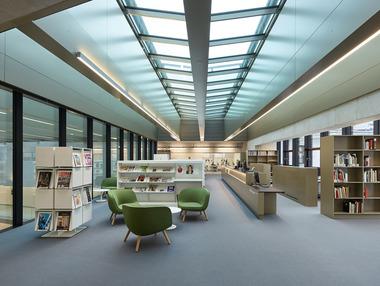 Die Bibliothek im 5. Obergeschoss liegt oberhalb des großen Veranstaltungssaals – von hier aus blickt man in den Luftraum der Aula