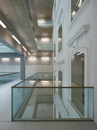 Das System aus Stahlbetonunterzügen und Pfeilern wird kraftschlüssig mit den Platten der umlaufenden Galerien verbunden, die wiederum den Übergang zum Altbau und damit eine horizontale Aussteifung bilden