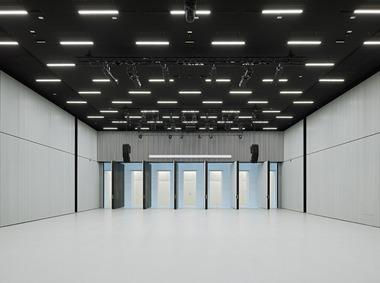 Der riesige Veranstaltungs- und Hörsaal befindet sich am Ende der Aula. Er ist durch elastische Lager akustisch von der darunter verlaufenden U-Bahn entkoppelt und kann zur Aula komplett geöffnet werden