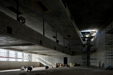 Der Rohbau zeigt bereits die Dimensionen des bis zu 9m hohen Kontrollraums – hier auf der Zwischenebene mit der vom Dach abgehängten Brücke. 60 Spannkabel stellen die ausreichende Vorspannung der weitspannenden Dachfläche sicher