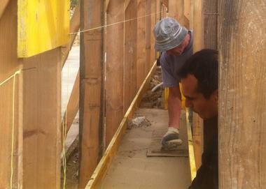 Der Blick zwischen die Schalung: Die Betonwände wachsen langsam aber stetig, die Handwerker betonieren Schicht für Schicht und setzen die Natursteinlagen