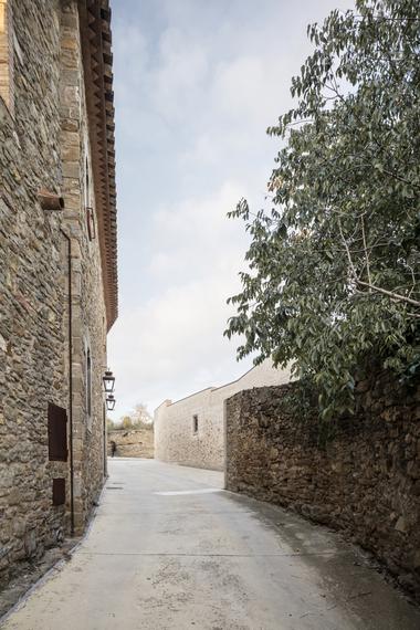 Die Straßenfront des neuen Ferienhauses wirkt so, als ob die alte Steinmauer nie abgerissen worden wäre