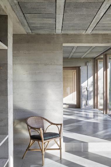 """Das Haus besteht aus einer monolithischen Betonkonstruktion. Innen prägen die glatt geschalten tragenden Sichtbetonwände die """"Korridorzone"""" hinter den Glasfronten"""