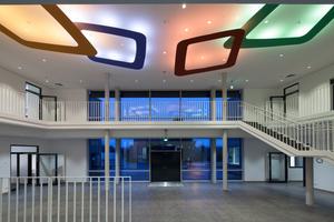 Der Eingangbereich wird als Wir-Raum bezeichnet. Bereits hier werden die abgehängten Ringe unter der Decke eingesetzt, die das Licht farbig an die Decke reflektieren